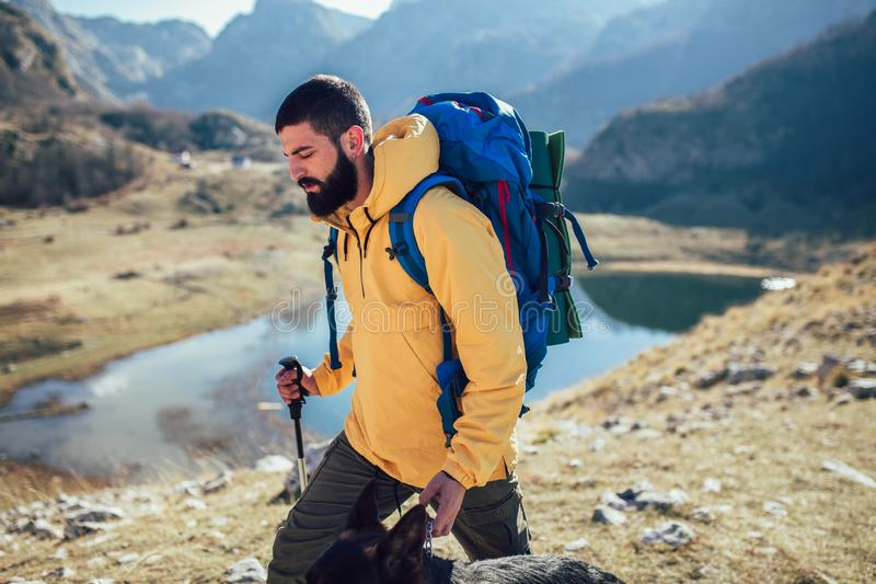 Man Traveler with backpack mountaineering . Travel Lifestyle concept lake and mountains on background Summer expedition vacations outdoor stock photo