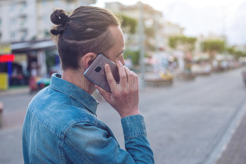 Man traveler with backpack talking on the phone in the background of the street. stock photography