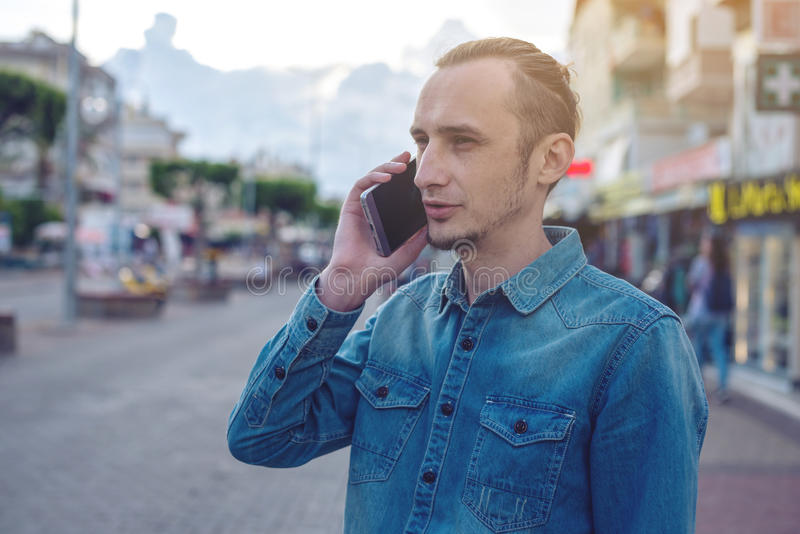 Man traveler with backpack talking on the phone in the background of the street. stock images