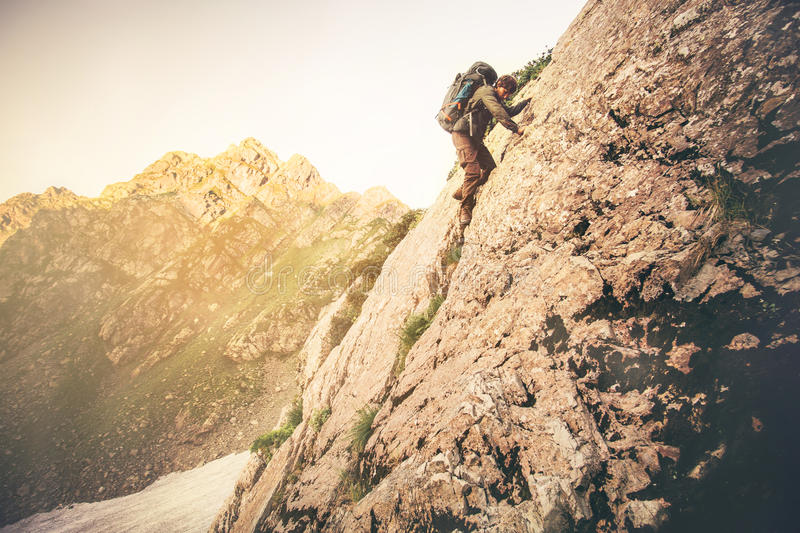 Man Traveler with big backpack climbing on rocks royalty free stock images
