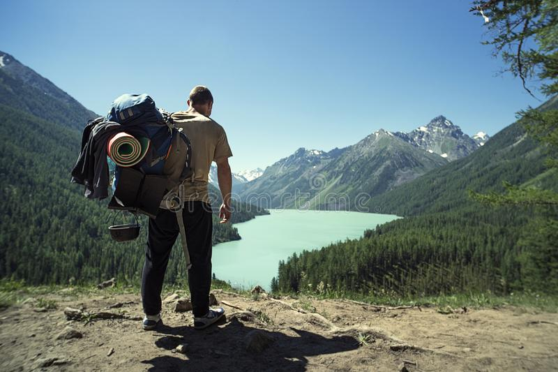 Man Traveler with big backpack mountaineering Travel Lifestyle concept lake and mountains on background Summer extreme vacations o stock photo
