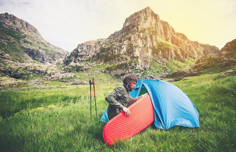 Man Traveler with camping equipment mattress and tent outdoor Travel Lifestyle. Concept rocky mountains landscape on background Summer journey adventure royalty free stock photography