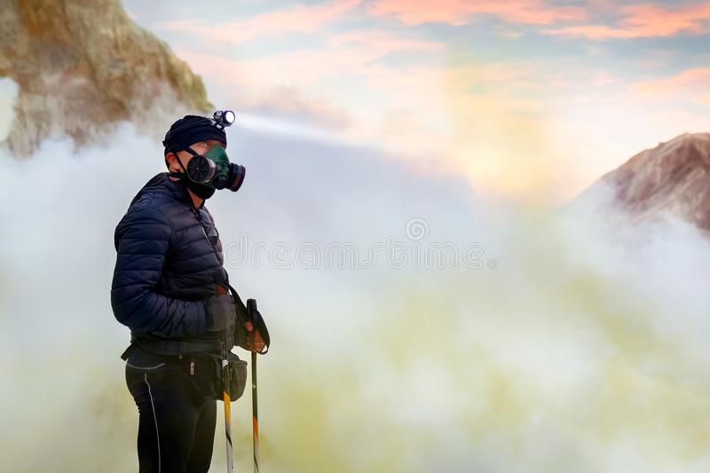 Man traveler in the crater of active volcano Ijen. Sulfur rocks, volcanic blue toxic lake and pink dawn. Gunung Ijen. stock photography
