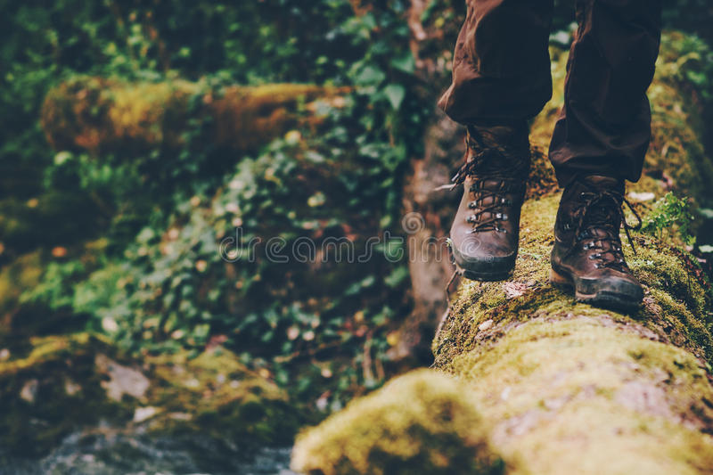 Man Traveler crossing over river on woods outdoor. In wild forest Lifestyle Travel extreme survival concept summer adventure vacations royalty free stock photo