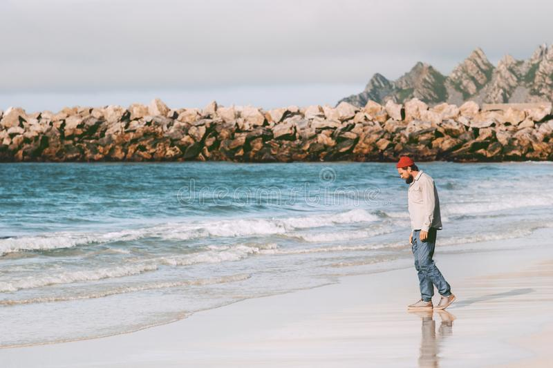 Man traveler enjoying ocean view on empty beach. Traveling in Norway active vacations outdoor journey lifestyle royalty free stock image