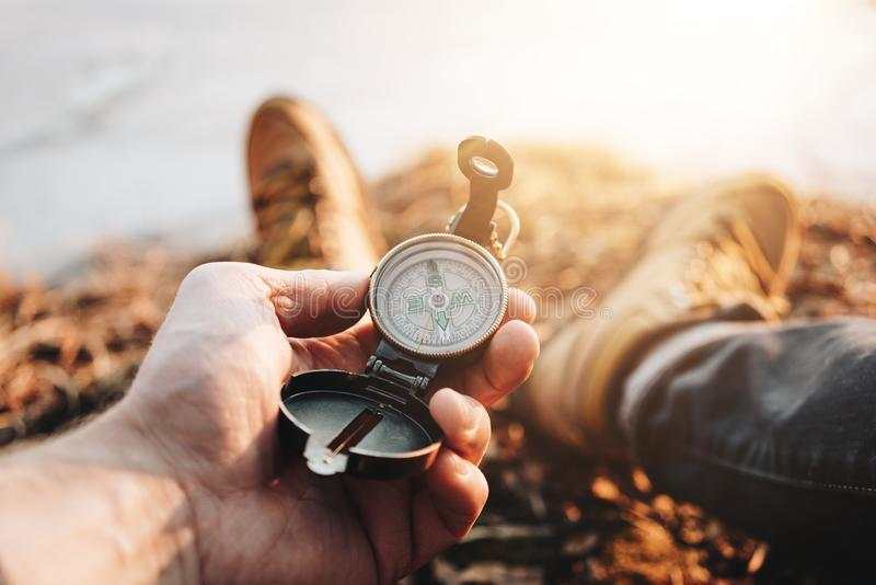 Man traveler hold compass in hand on background legs in hiking boots. Blurred background stock photo
