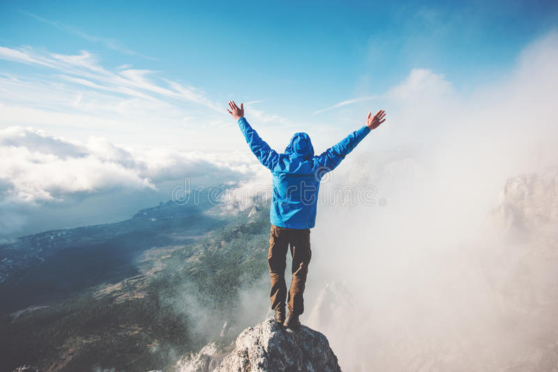 Man Traveler on mountain summit enjoying aerial view. Hands raised over clouds Travel Lifestyle success concept adventure active vacations outdoor happiness royalty free stock images