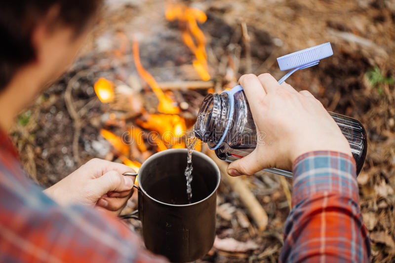 Man traveler pours water from a bottle into a metal mug. Bushcraft, adventure, travel, tourism and camping concept stock photo