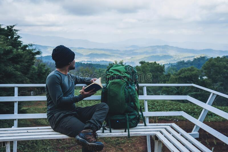 Man traveler is reading book travels nature on the mountain In the fresh air in the north, Chiang Mai in Thailand royalty free stock photo