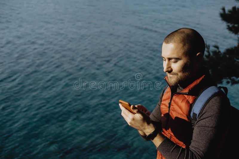 Man traveler in a red waistcoat watching world map on mobile phone while relaxing near sea stock photos