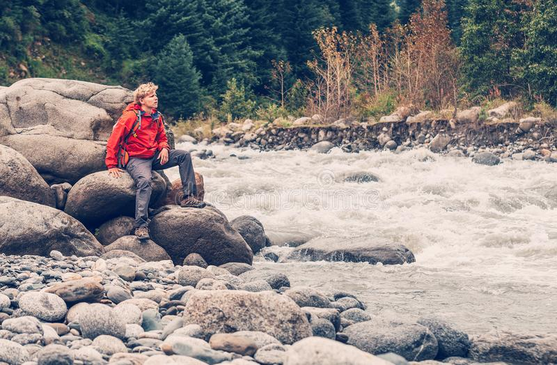 Man traveler sits on mountain river bank royalty free stock photography