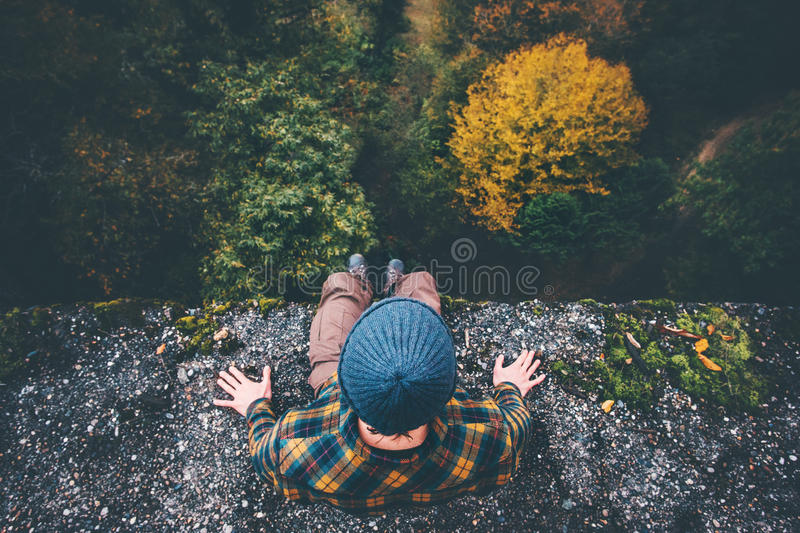 Man Traveler sitting on cliff bridge edge. With forest aerial view Travel Lifestyle adventure vacations concept stock image