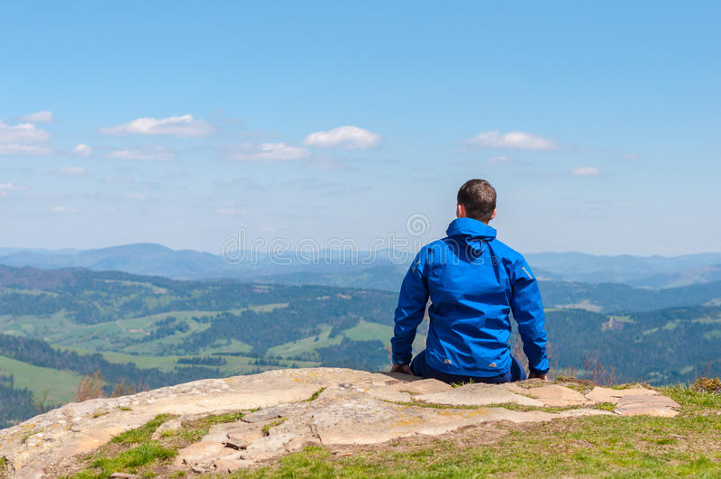 Man, traveler sitting on the edge of a cliff and. Traveler is looking at the silhouette of the mountains on the horizon. Man sitting on the edge of a cliff and stock photos