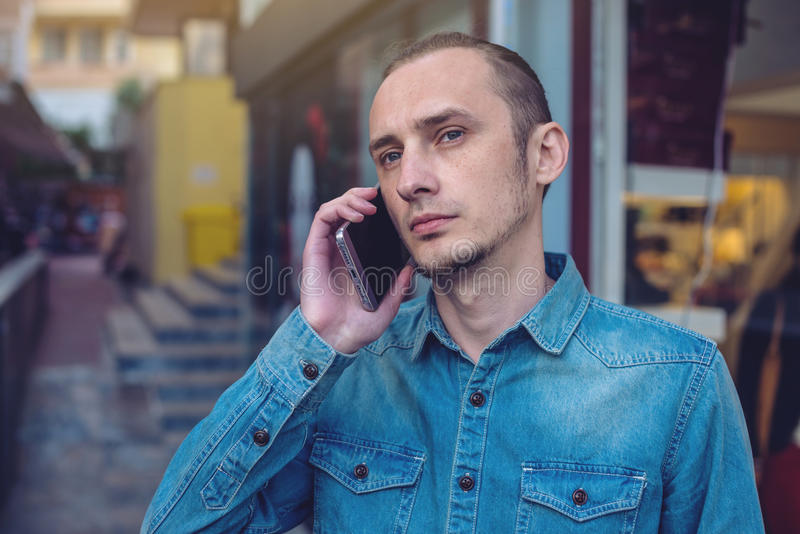 Man traveler talking on the phone in the background of the street. royalty free stock photography