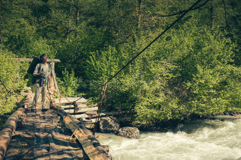 A man traveling with backpack hiking on bridge over river. Travel Lifestyle concept. royalty free stock photos