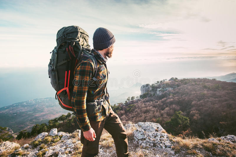 Man traveling with backpack hiking in mountains stock images