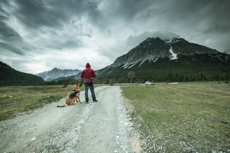 Man traveling with dog in Switzerland on rural road in mountains royalty free stock image