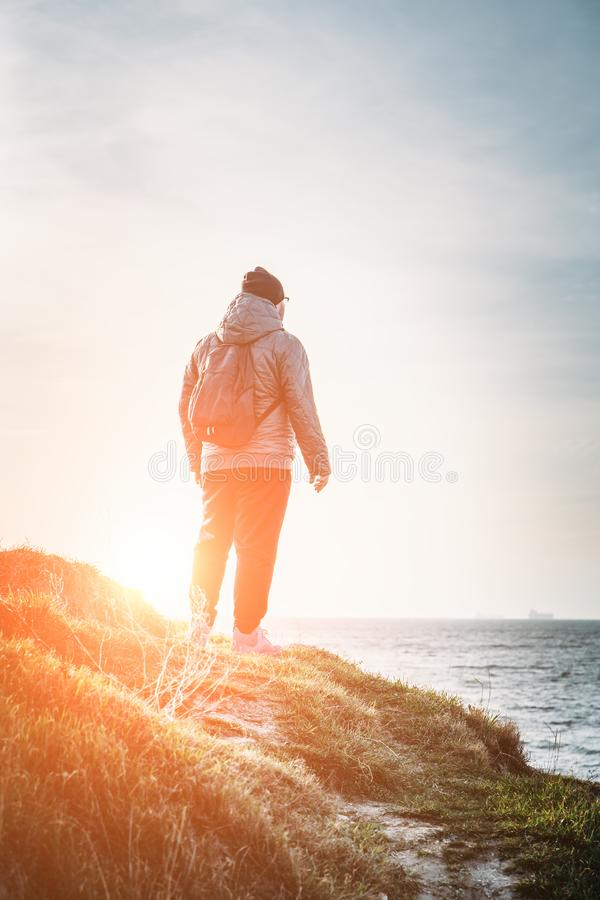 Man traveller with backpack stands on top of rock cliff in grass and looking at sea landscape at sunset, freedom of adventure stock image
