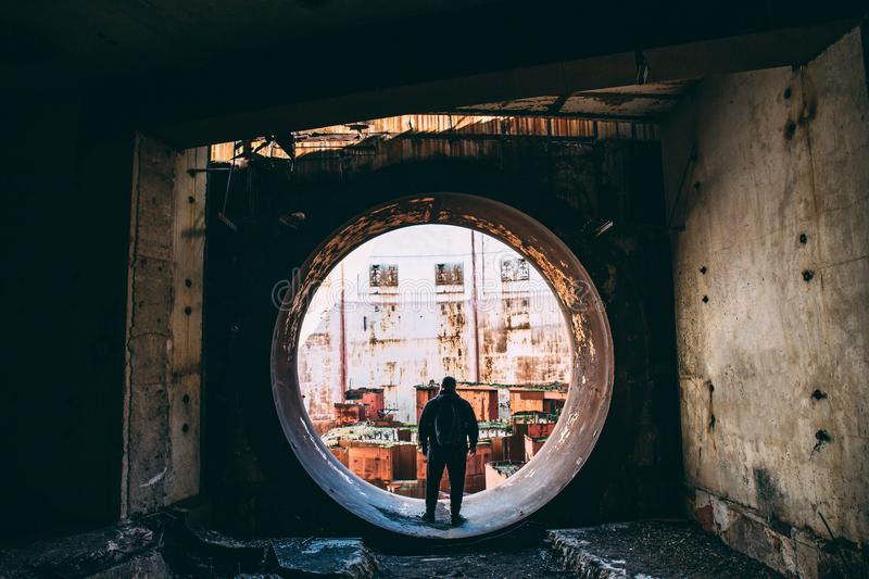 Man traveller and explorer inside round door or gate to abandoned nuclear rector or generator room in ruined NPPlant stock photo