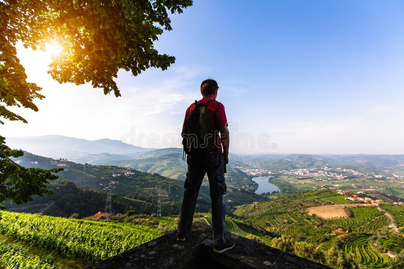 Man traveller stands on a cliff overlooking of river, the vineyards are on a hills Douro Valley royalty free stock photography
