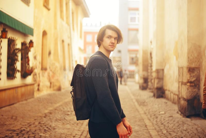 A man travels in Europe. A man smiles, walks through the streets of the old city, with a briefcase. stock photo