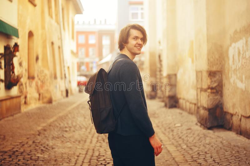 A man travels in Europe. A man smiles, walks through the streets of the old city, with a briefcase. stock photography
