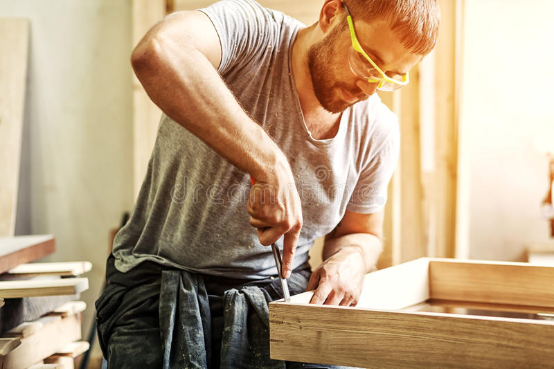 Man treating a wooden product with a chisel. A dark-haired man with a beard and protective green glasses treating a wooden product with a chisel in the workshop royalty free stock images