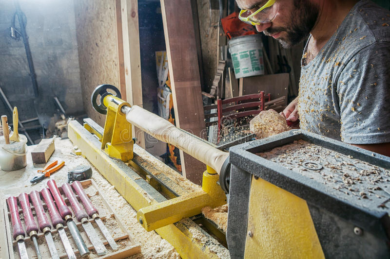 Man treating a wooden product with a chisel. A dark-haired man with a beard and protective green glasses treating a wooden product with a chisel in the workshop royalty free stock image