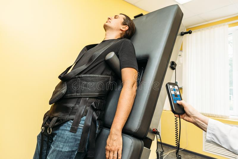 Man on treatment recovery physiotherapy of human spine by stretching with special medical equipment in clinic stock photos