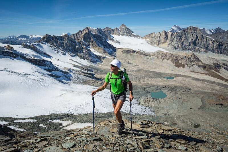 Man trekking in the Alps in a beautiful sunny day. Grand Paradiso National Park. Italy royalty free stock images