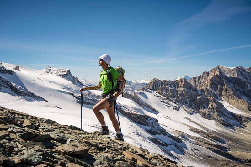 Man trekking in the Alps in a beautiful sunny day. Grand Paradiso National Park. Italy royalty free stock image