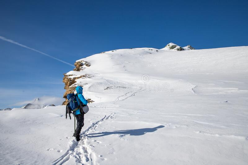 man trekking in snow in the Swiss Alps royalty free stock photos