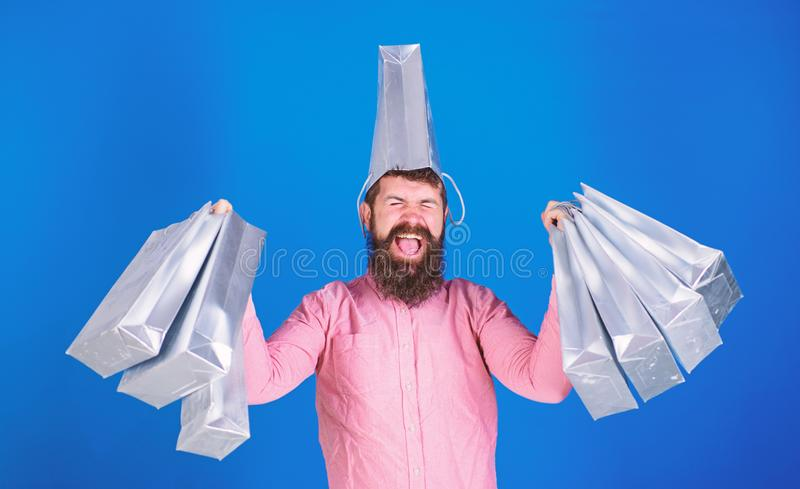 Man with trendy beard wearing pink shirt and silver bag on his head on blue background. Shopping champion. Winning first prize in contest, happiness concept stock photo