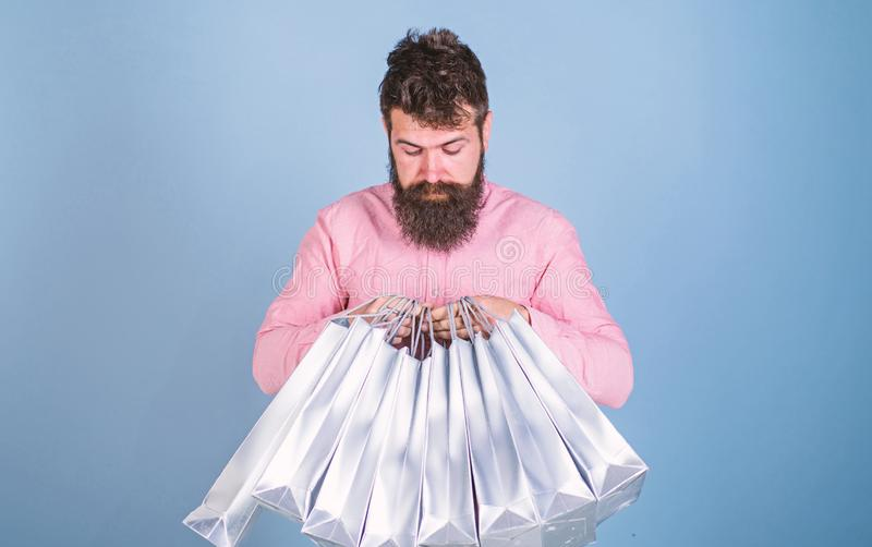 Man with trendy hairstyle and beard holding silver bags. Hipster in pink shirt with curious look isolated on blue. Background. Concentrated bearded man opening stock photography