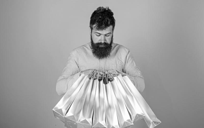 Man with trendy hairstyle and beard holding silver bags. Hipster in pink shirt with curious look isolated on blue. Background. Concentrated bearded man opening stock photo