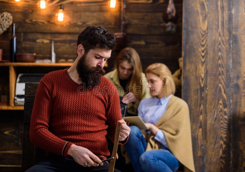 Man with trendy hipster beard whetting knife blade with old leather belt. Bearded man sharpening razor, barbershop. Man with trendy hipster beard whetting knife royalty free stock photo