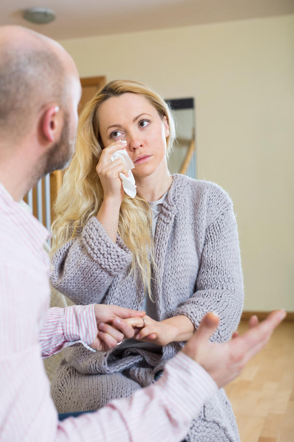 Man tries reconcile with woman. Man tries reconcile with women in home. Focus on girl stock image