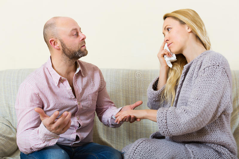 Man tries reconcile with woman. Man tries reconcile with young blonde women after quarrel. Focus on girl royalty free stock image