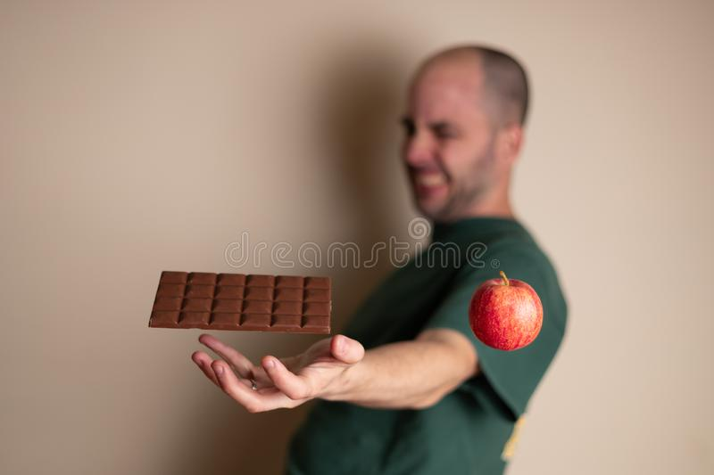 Man tries to grab a chocolate bar with one hand and ignoring the healthy option stock photo