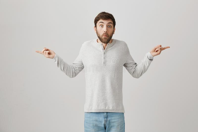 Man tries to look uninvolved. Portrait of confused and questioned man with beard spreading hands and pointing in both. Sides with troubled expression as if he stock image