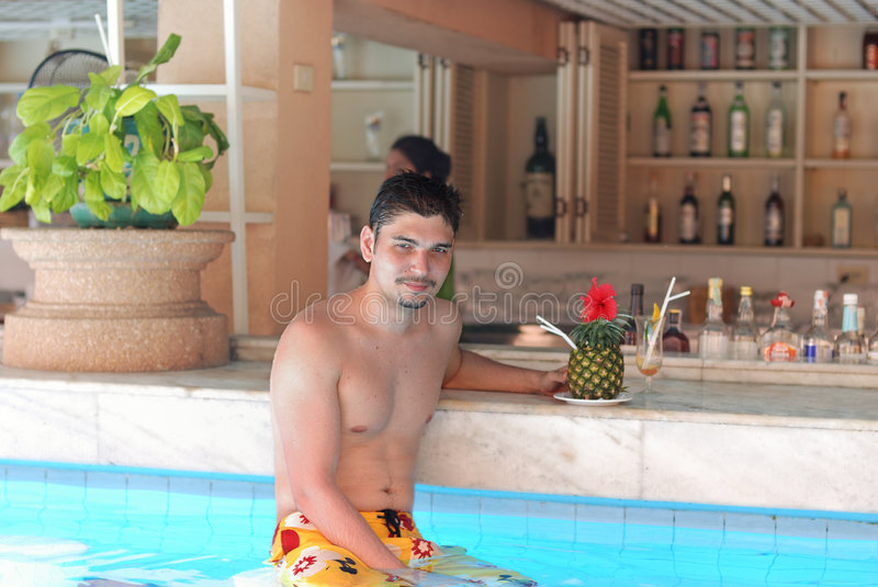 Man in tropical pool bar. With cocktail stock photography
