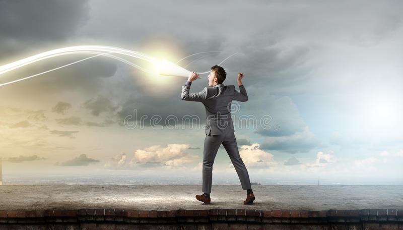Man with trumpet. Young businessman screaming emotionally in paper trumpet stock photography