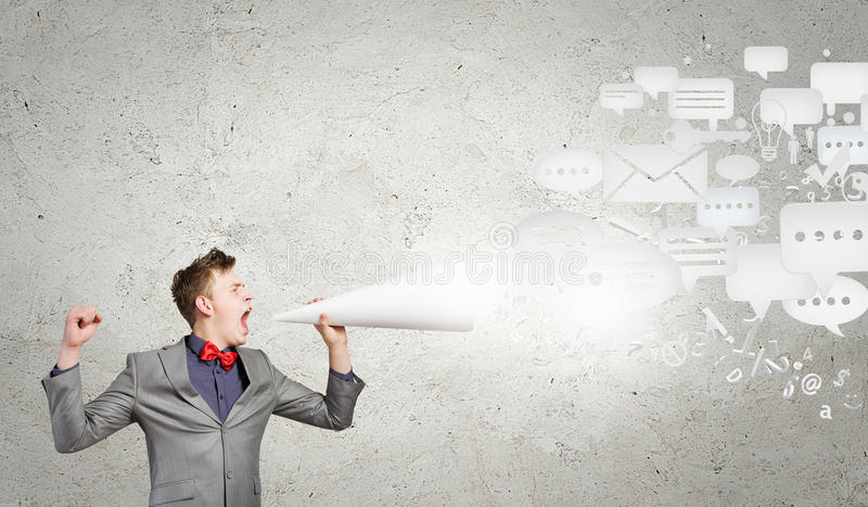 Man with trumpet. Young excited businessman screaming in paper trumpet stock images