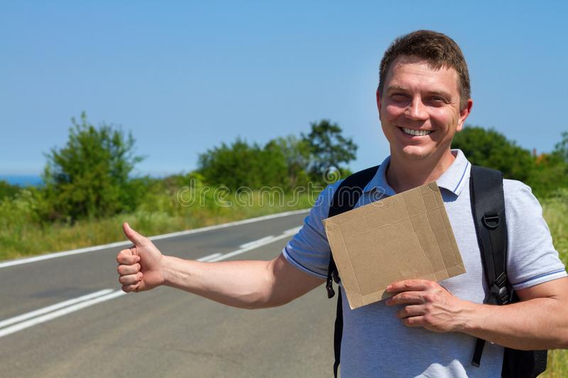 Man try to stop car with cardboard sign royalty free stock photo