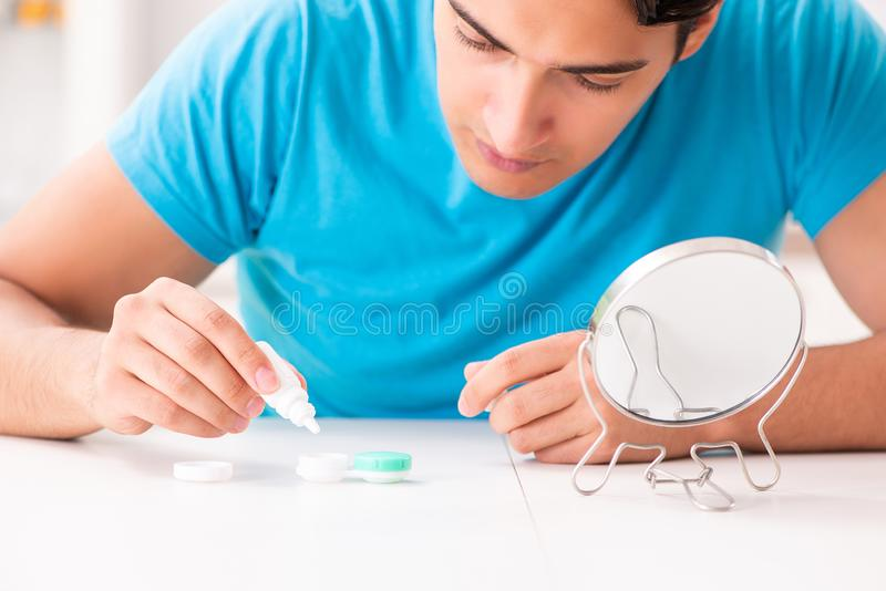 The man trying contact lenses at home. Man trying contact lenses at home stock photo