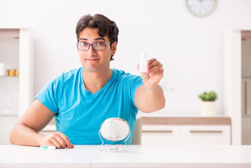 The man trying contact lenses at home. Man trying contact lenses at home royalty free stock photo