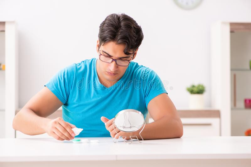 The man trying contact lenses at home. Man trying contact lenses at home royalty free stock images