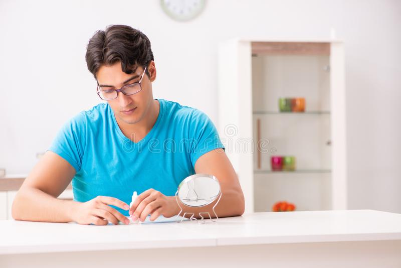 The man trying contact lenses at home. Man trying contact lenses at home stock photos