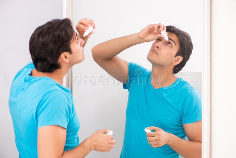 The man trying contact lenses at home. Man trying contact lenses at home stock image