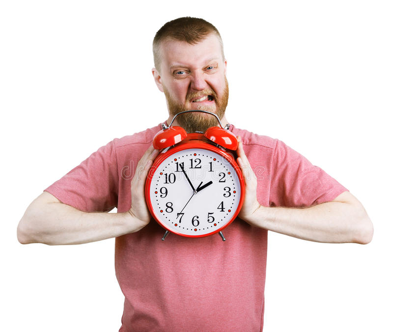 Man trying to break a big alarm clock. Angry man trying to break a big alarm clock royalty free stock photo